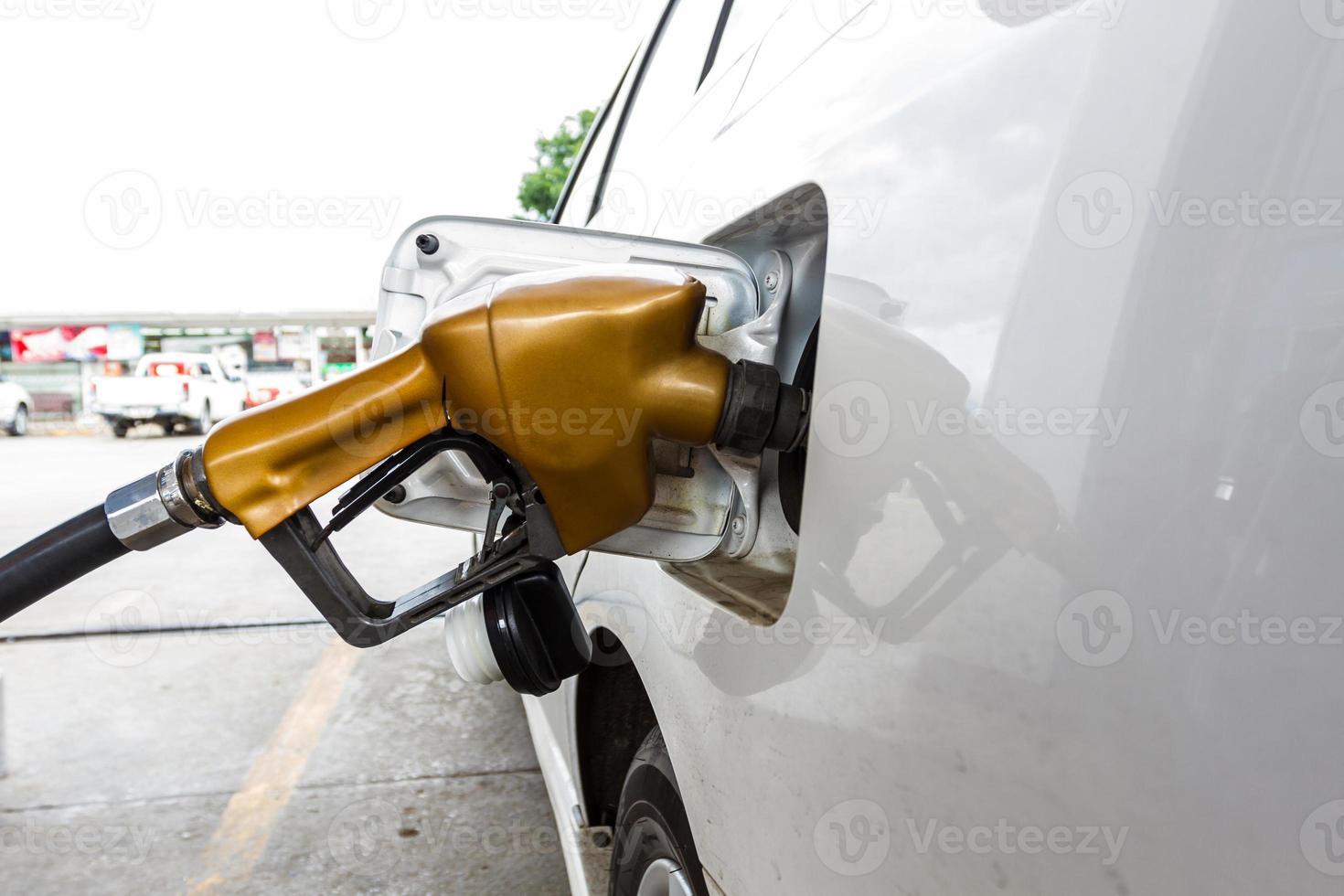 goldene Kraftstoffdüse, die ein weißes Auto füllt foto