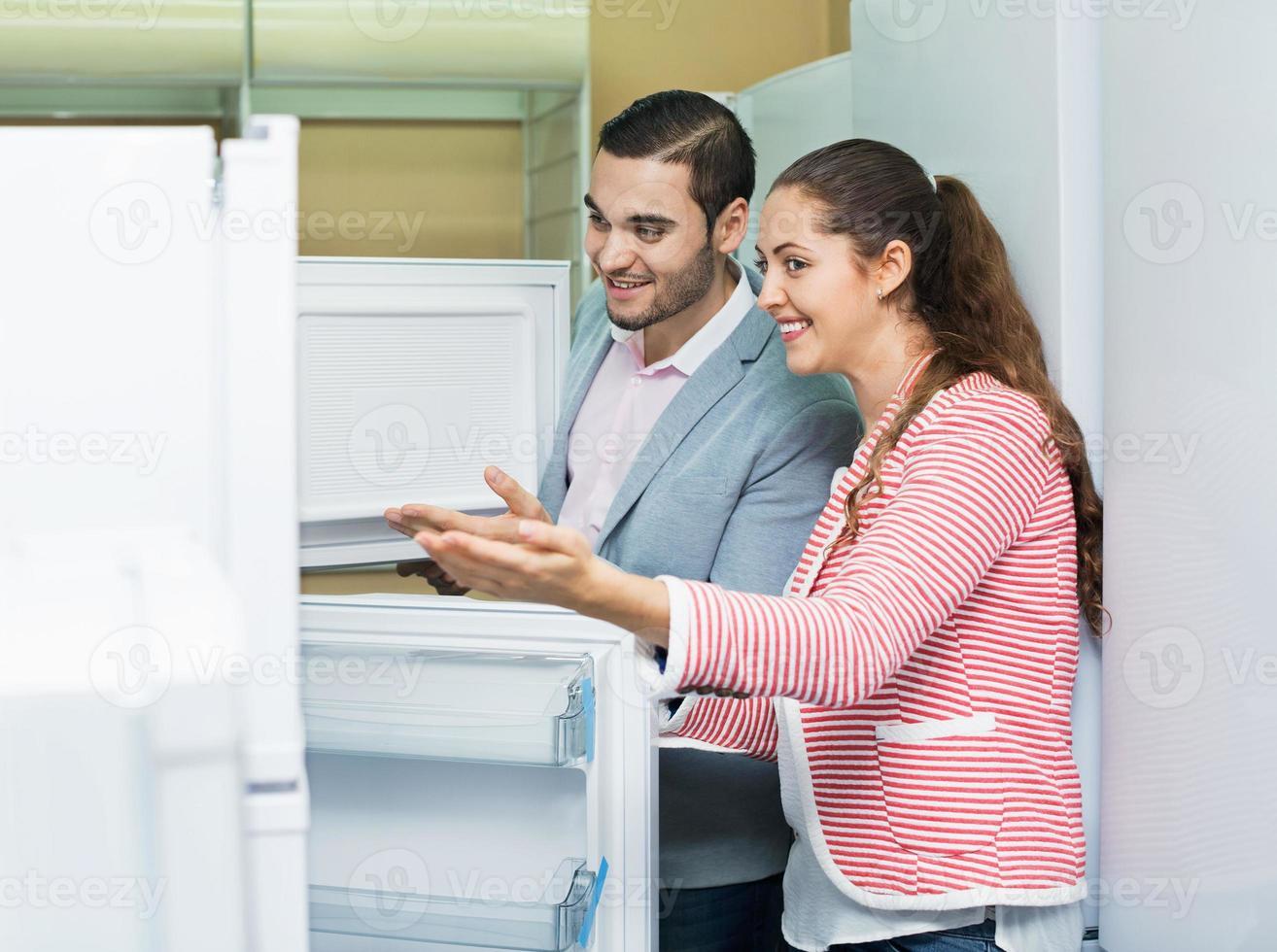 zufriedenes Paar mit Blick auf große Kühlschränke foto