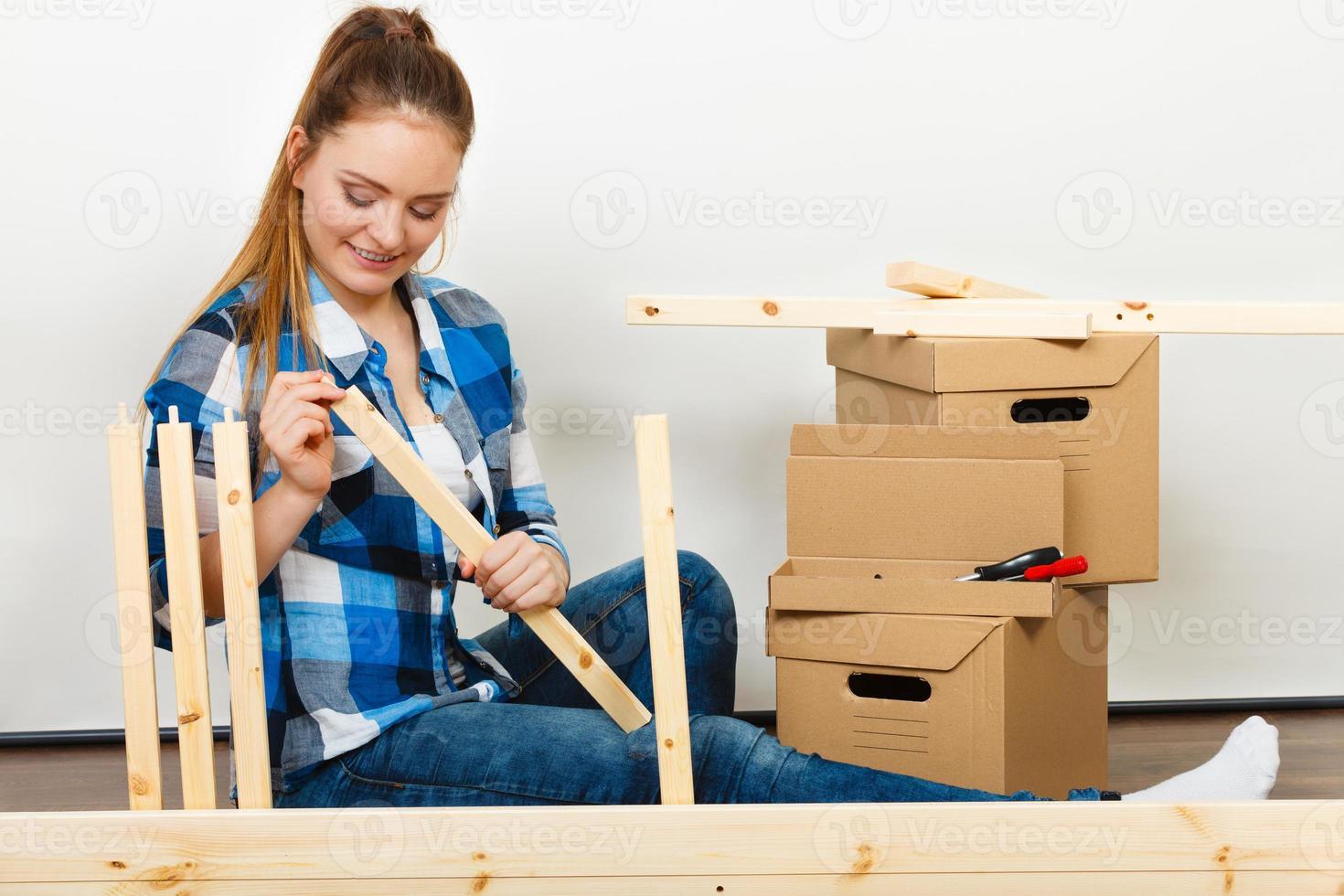 Frau zieht in Wohnungsmontagemöbel ein. foto