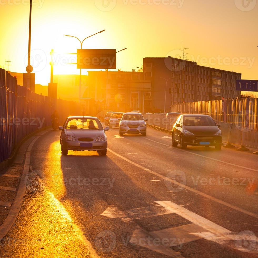 Autos in Bewegung verwischen auf der Straße während des Sonnenuntergangs, Peking China foto