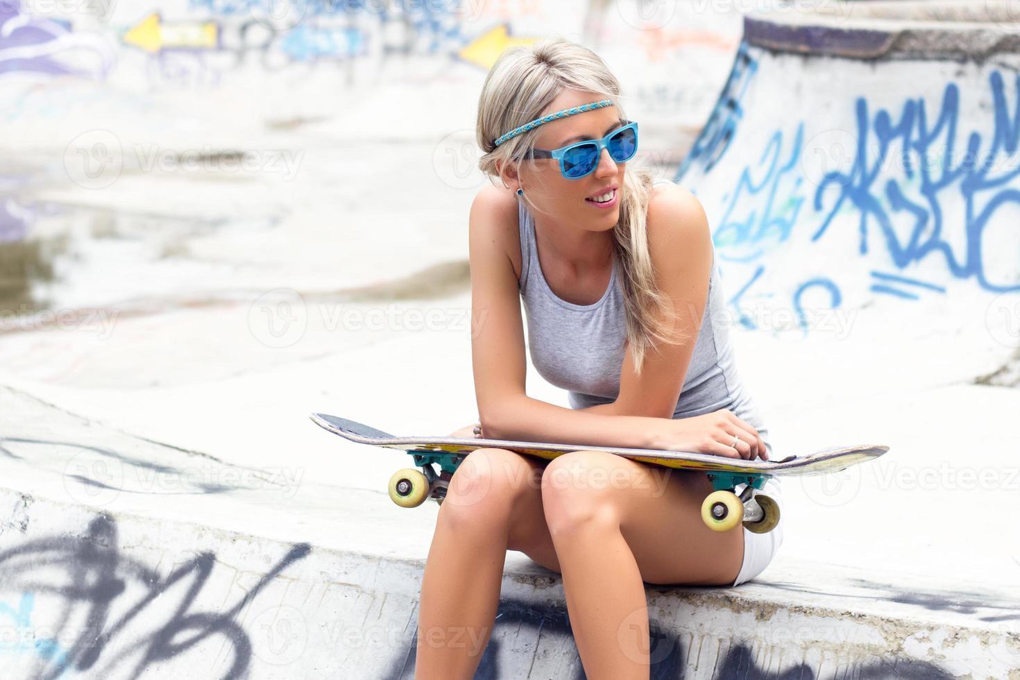 junges Mädchen mit Skateboard, das im Skatepark sitzt foto