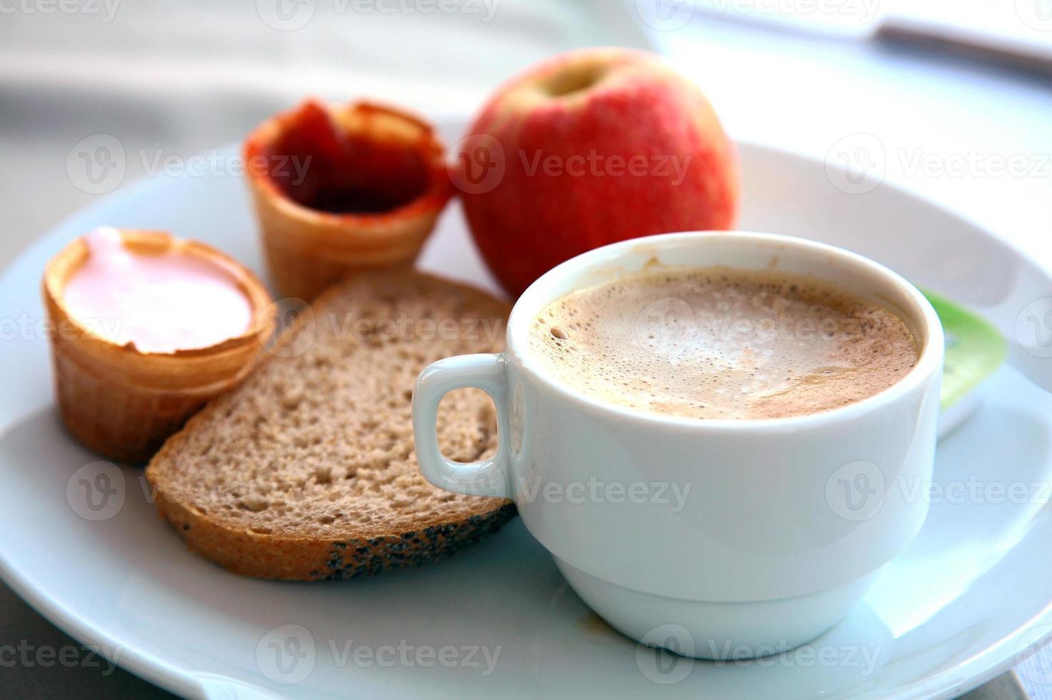 Tasse Cappuccino mit Obst, Joghurt und Brot foto