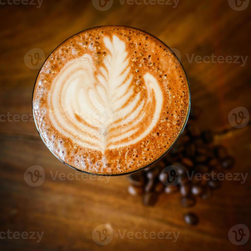 Latte Art und Kaffeebohnen auf Holz foto