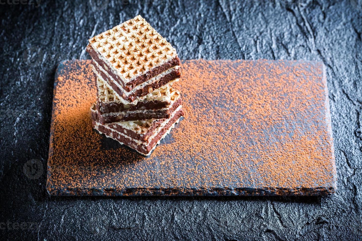 hausgemachte Waffeln mit Schokolade und Haselnuss auf Steinplatte foto