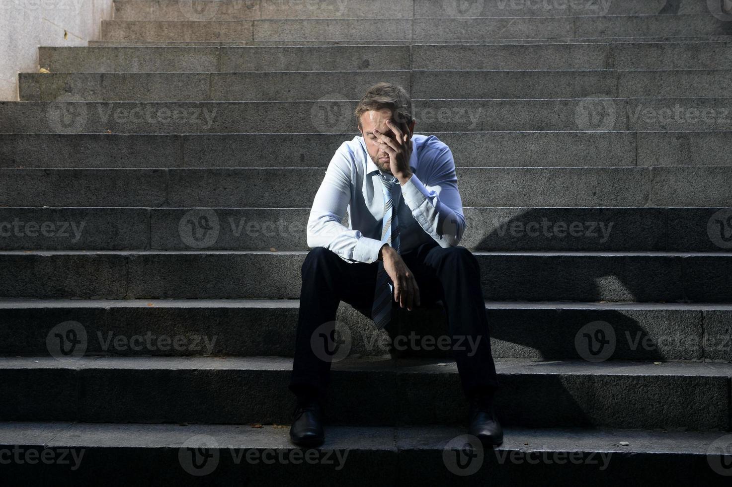 Geschäftsmann weint verloren in der Depression, die auf Straßenbetontreppen sitzt foto
