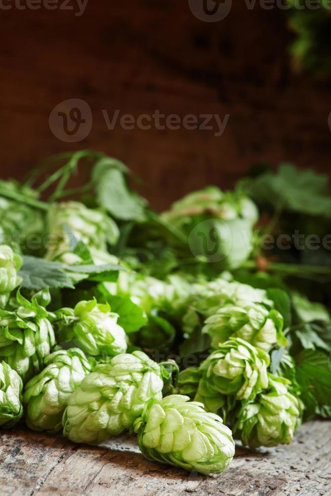 grüne Hopfenzapfen mit Blättern auf dem alten Holztisch foto