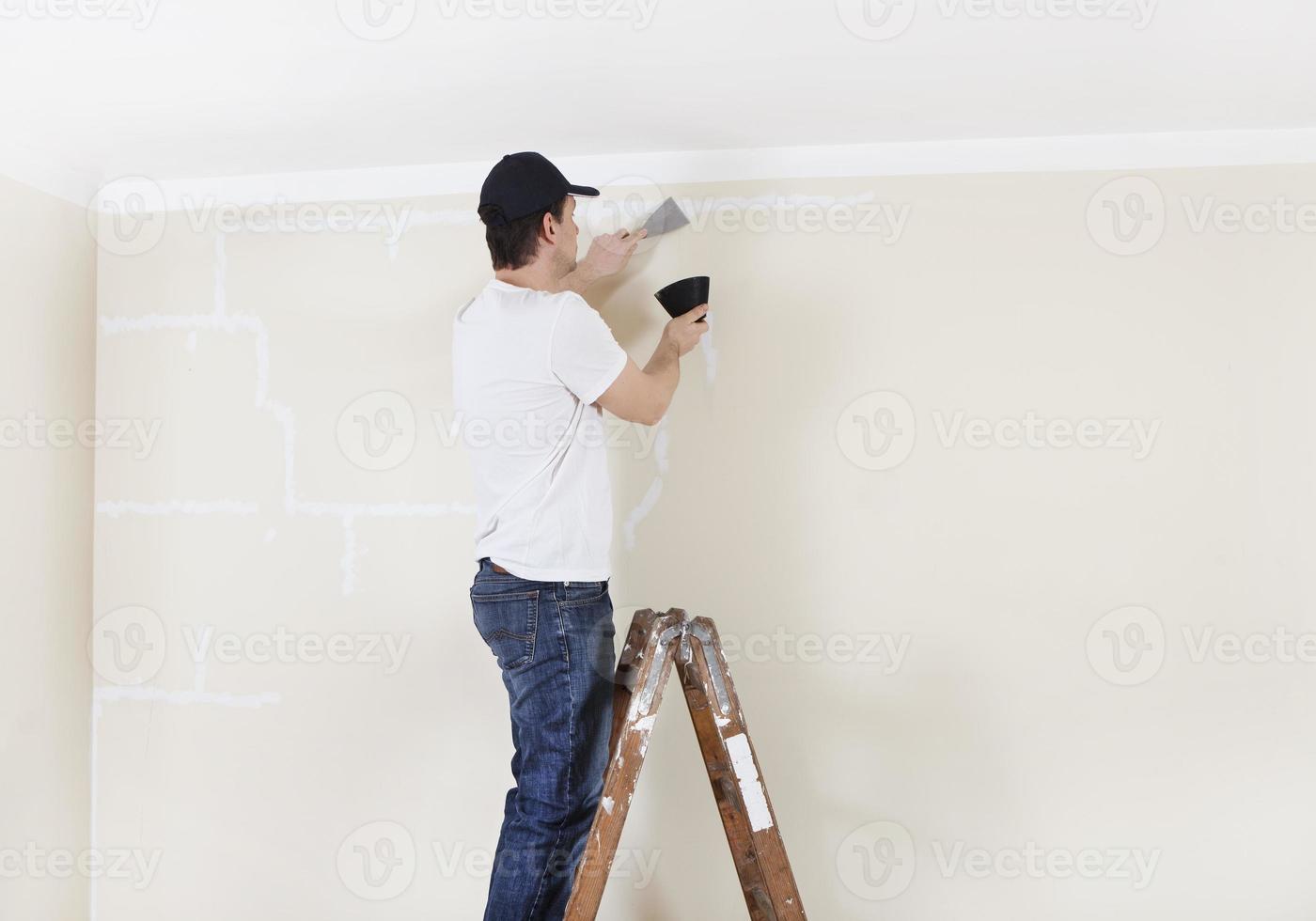 Mann auf Leiter spachtelt Wand foto