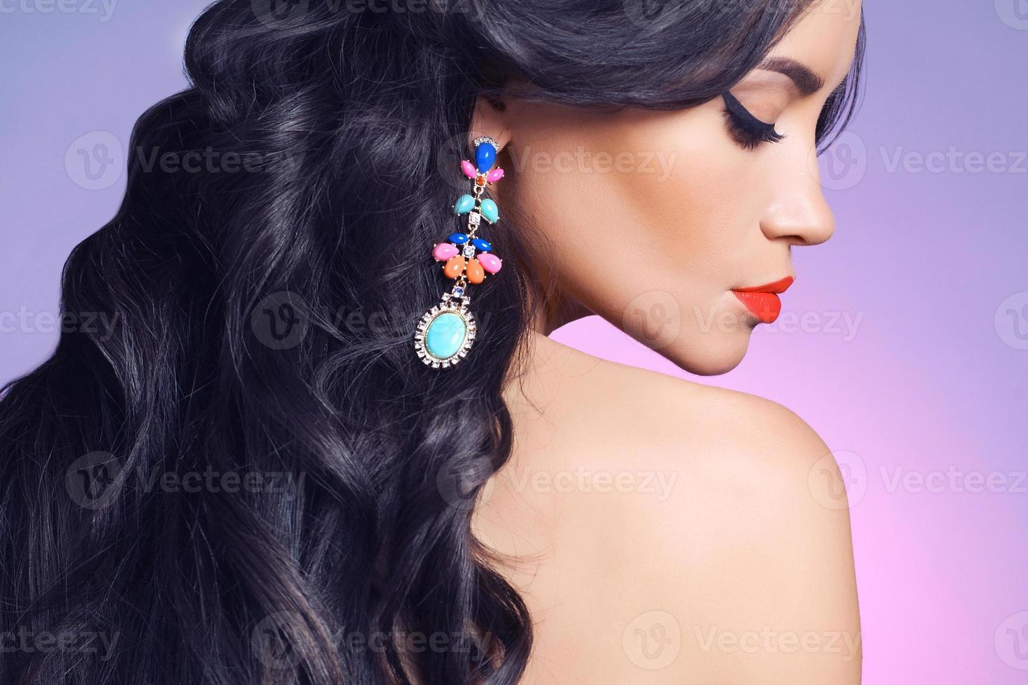 Seitenprofil der Frau, die einen bunten Ohrring trägt foto