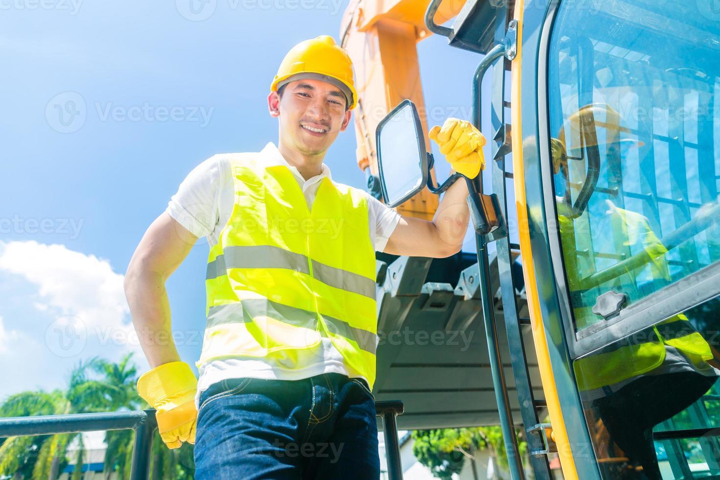 asiatischer Baumeister mit Bagger auf der Baustelle foto