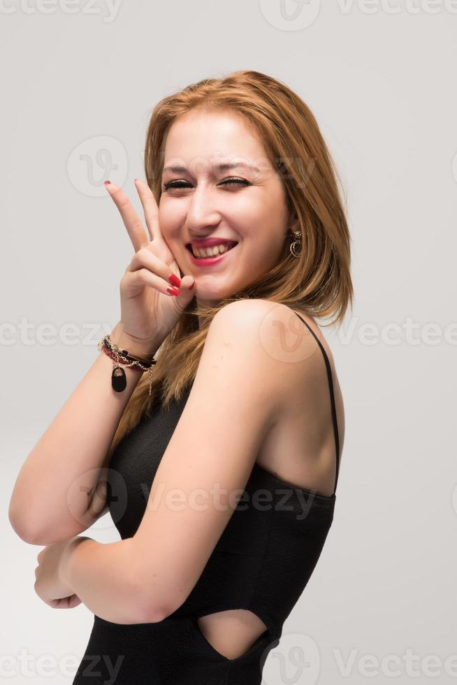glückliches und zufriedenes junges Mädchen, das mit ihr Siegesgeste zeigt foto