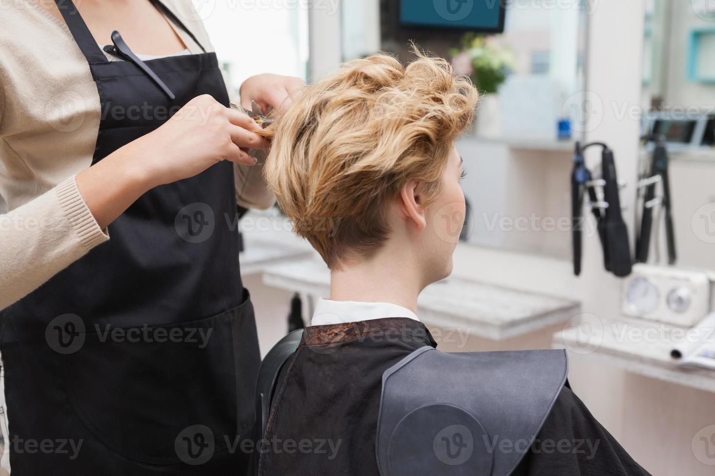 glücklicher Friseur, der einem Kunden die Haare schneidet foto