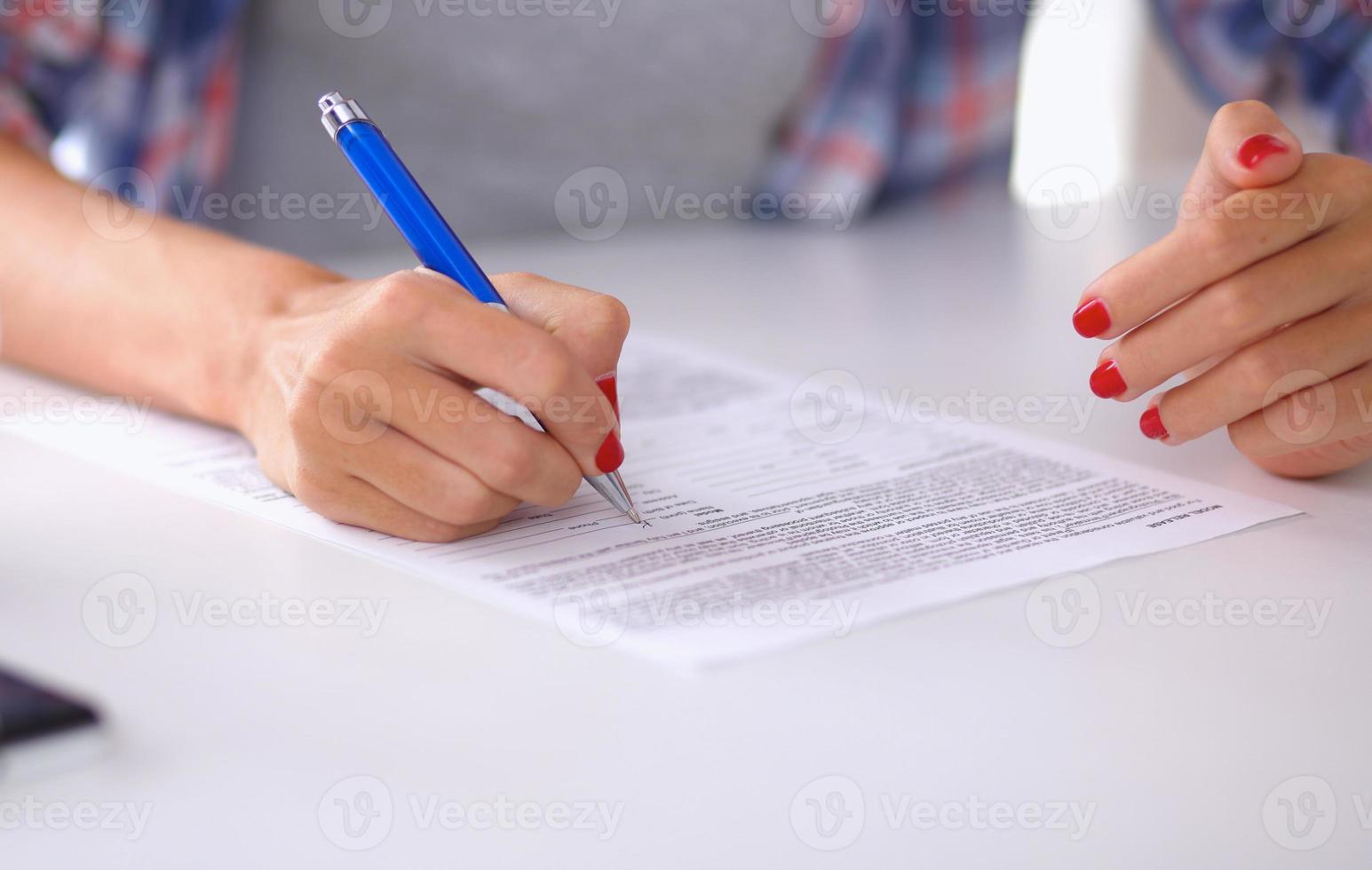 junge Frau, die etwas in ihren Notizblock schreibt foto