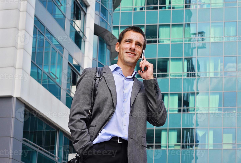 junger Geschäftsmann, der am Telefon in der Stadt spricht foto