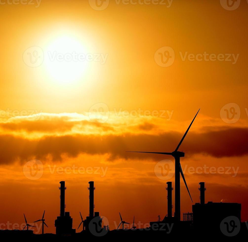 intensive Morgensonne über Kraftwerk mit Windmühlen, farbiges Bild foto