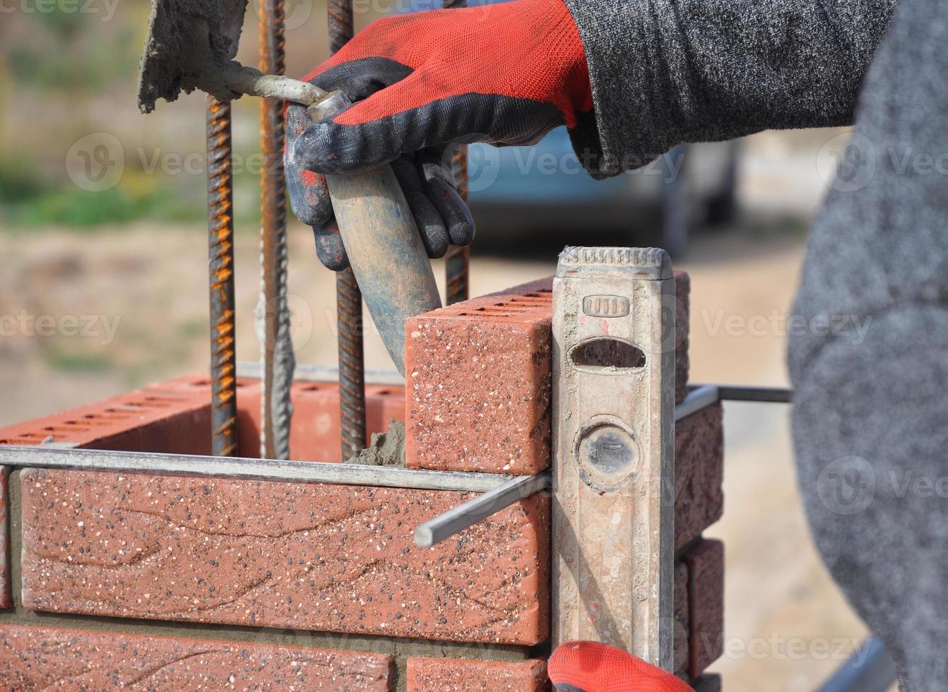 Maurer Arbeiter, der rote Blöcke installiert foto