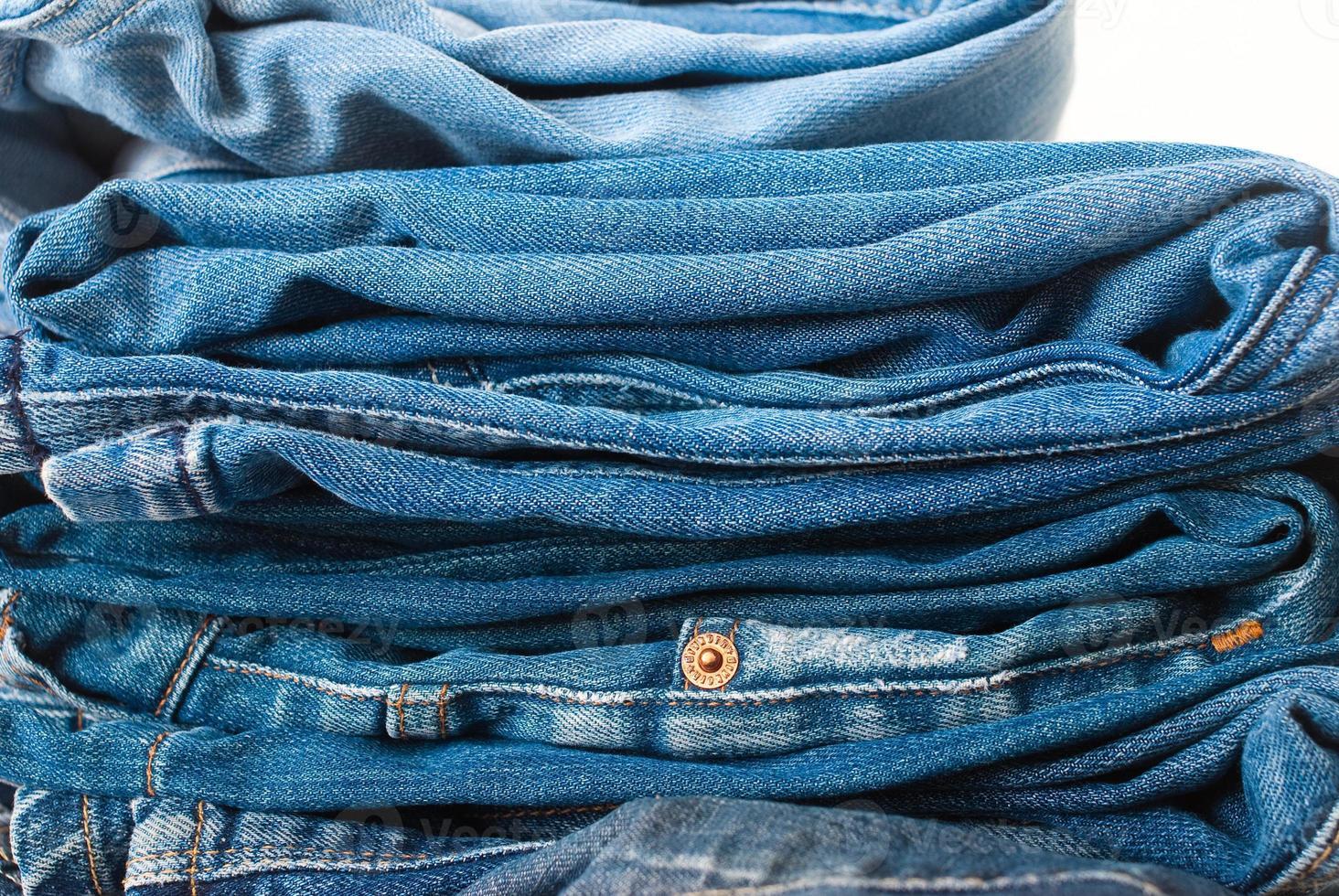 Jeans auf weißem Hintergrund gestapelt - Studioaufnahme foto