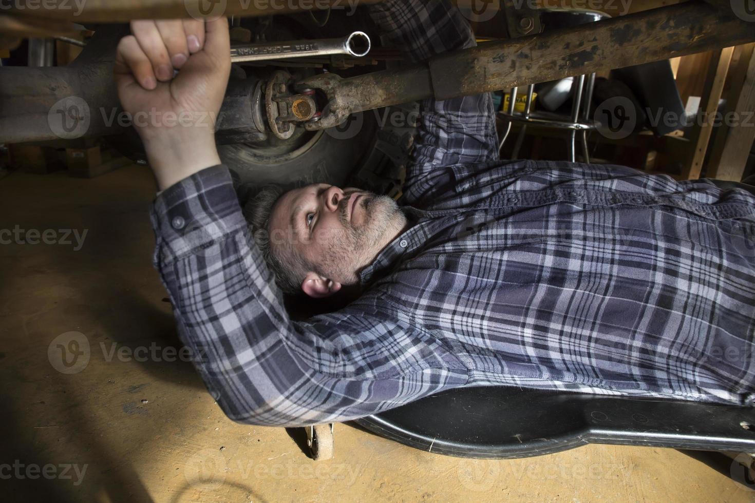 Mann arbeitet unter Auto mit Schraubenschlüssel foto
