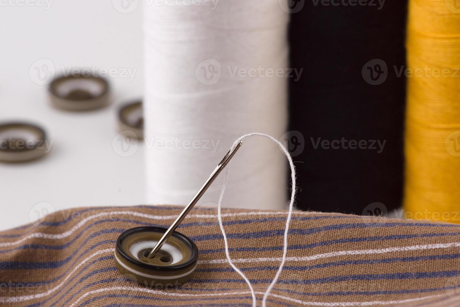 Knöpfe mit einem Faden und einer Nadel foto