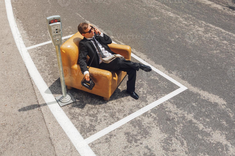 Geschäftsmann, der auf Sessel mitten auf der Straße sitzt foto