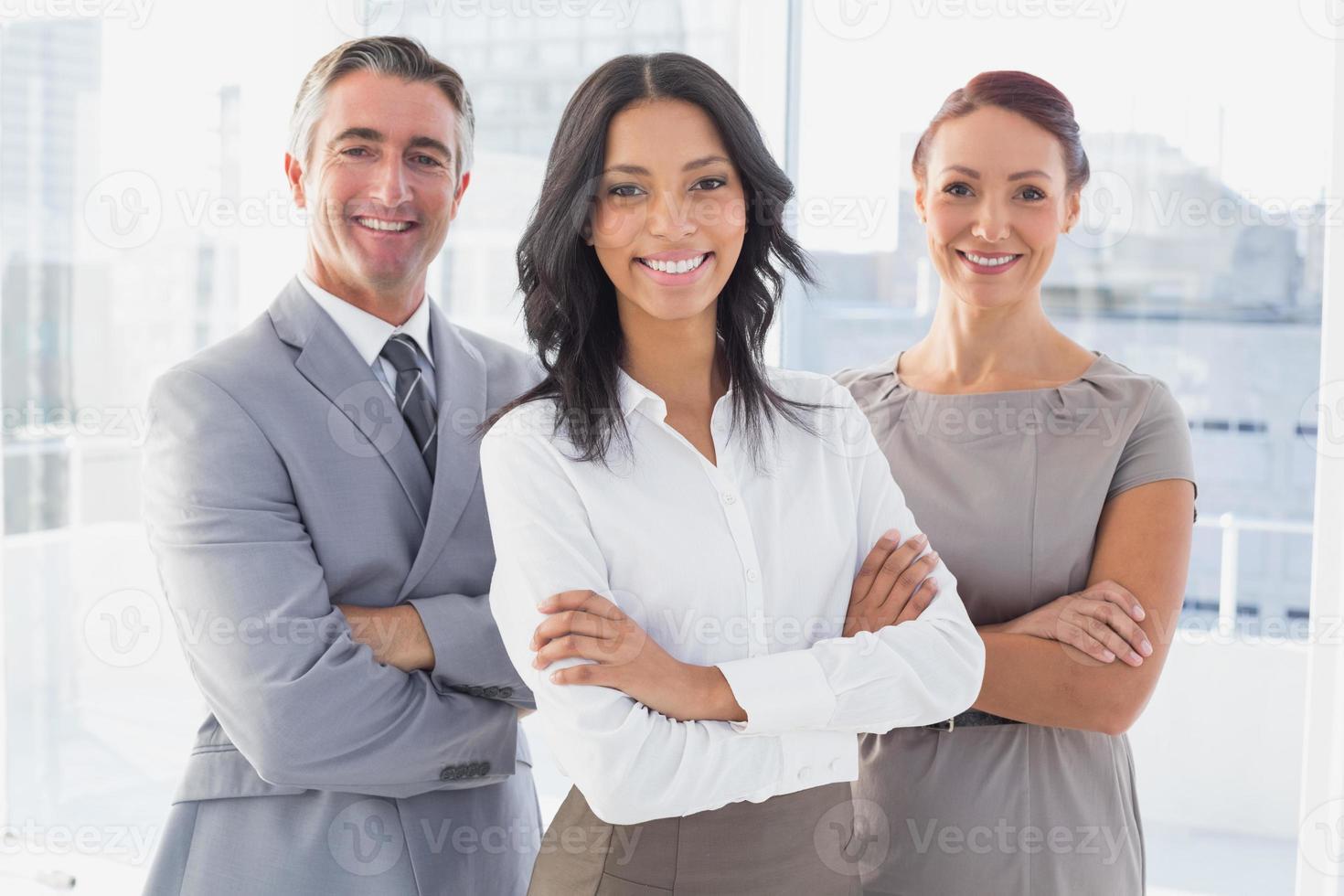 Geschäftsfrau lächelt mit verschränkten Armen foto
