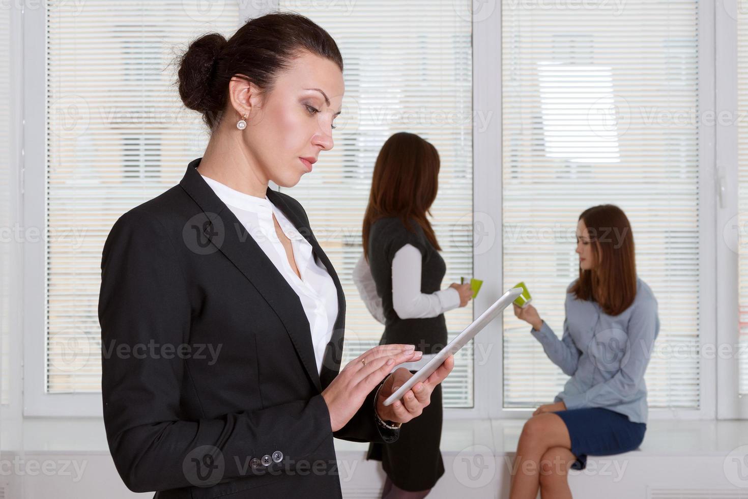 Frau in formeller Kleidung, die Informationen von der Tafel liest foto