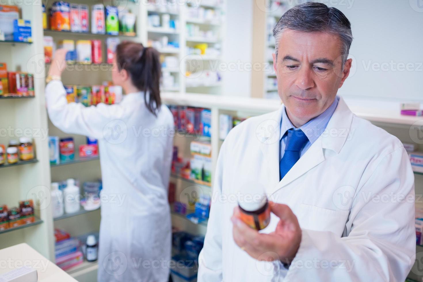 Mann hält eine Schachtel Pillen beim Lesen des Etiketts foto