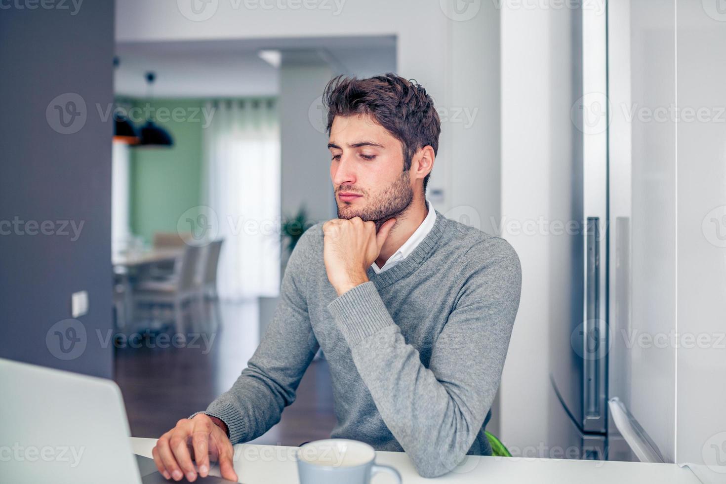 schöner junger konzentrierter Geschäftsmann, der von zu Hause aus arbeitet foto