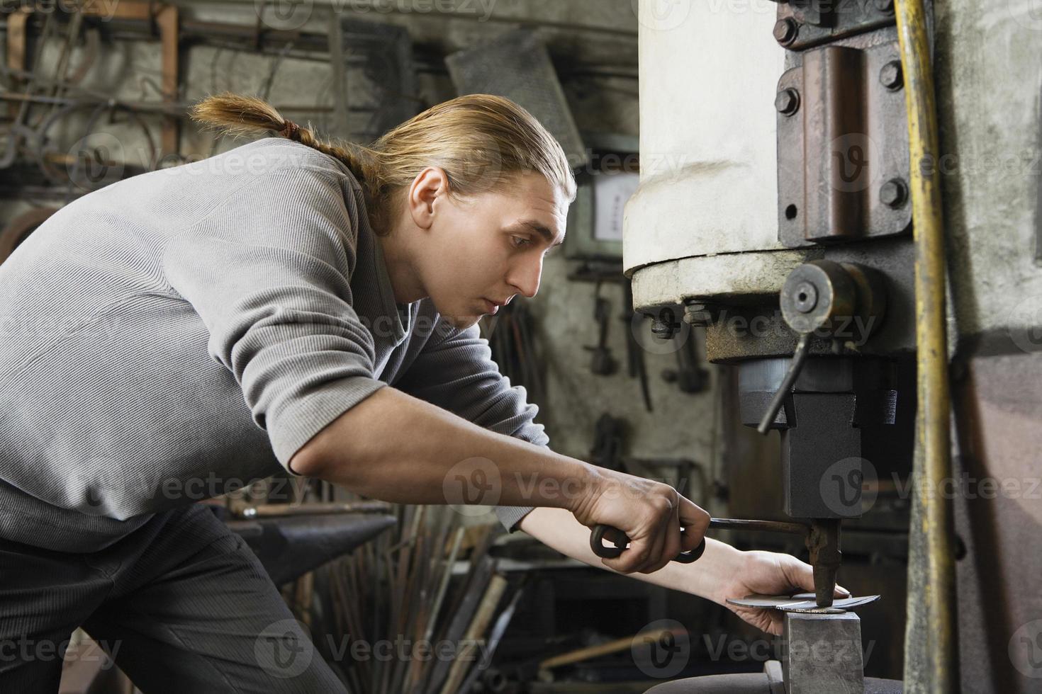 Schmied arbeitet in der Werkstatt foto