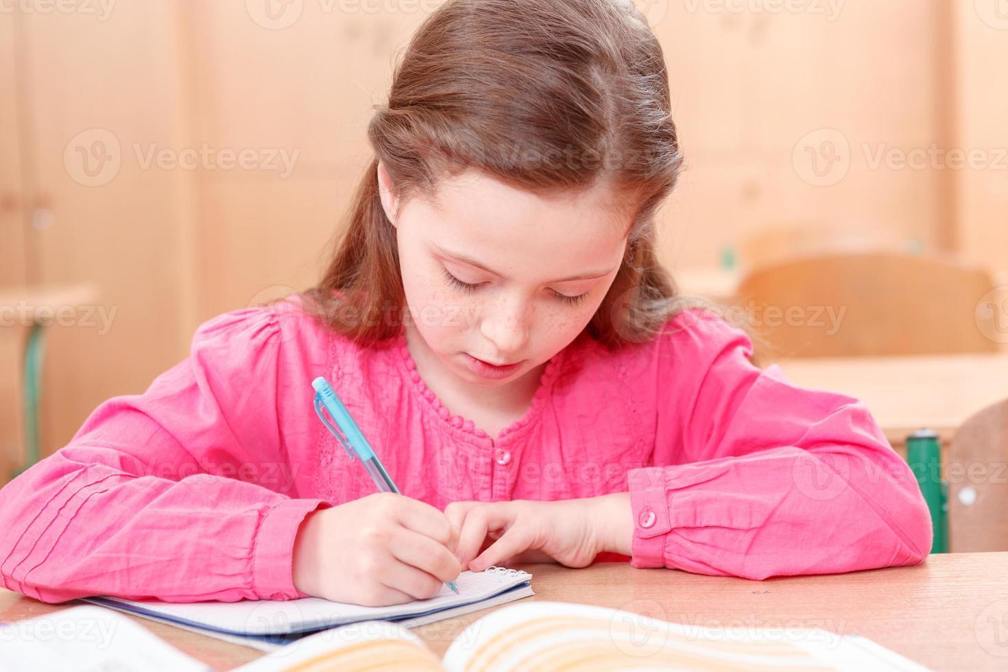 kleines schreibendes Mädchen während des Unterrichts foto