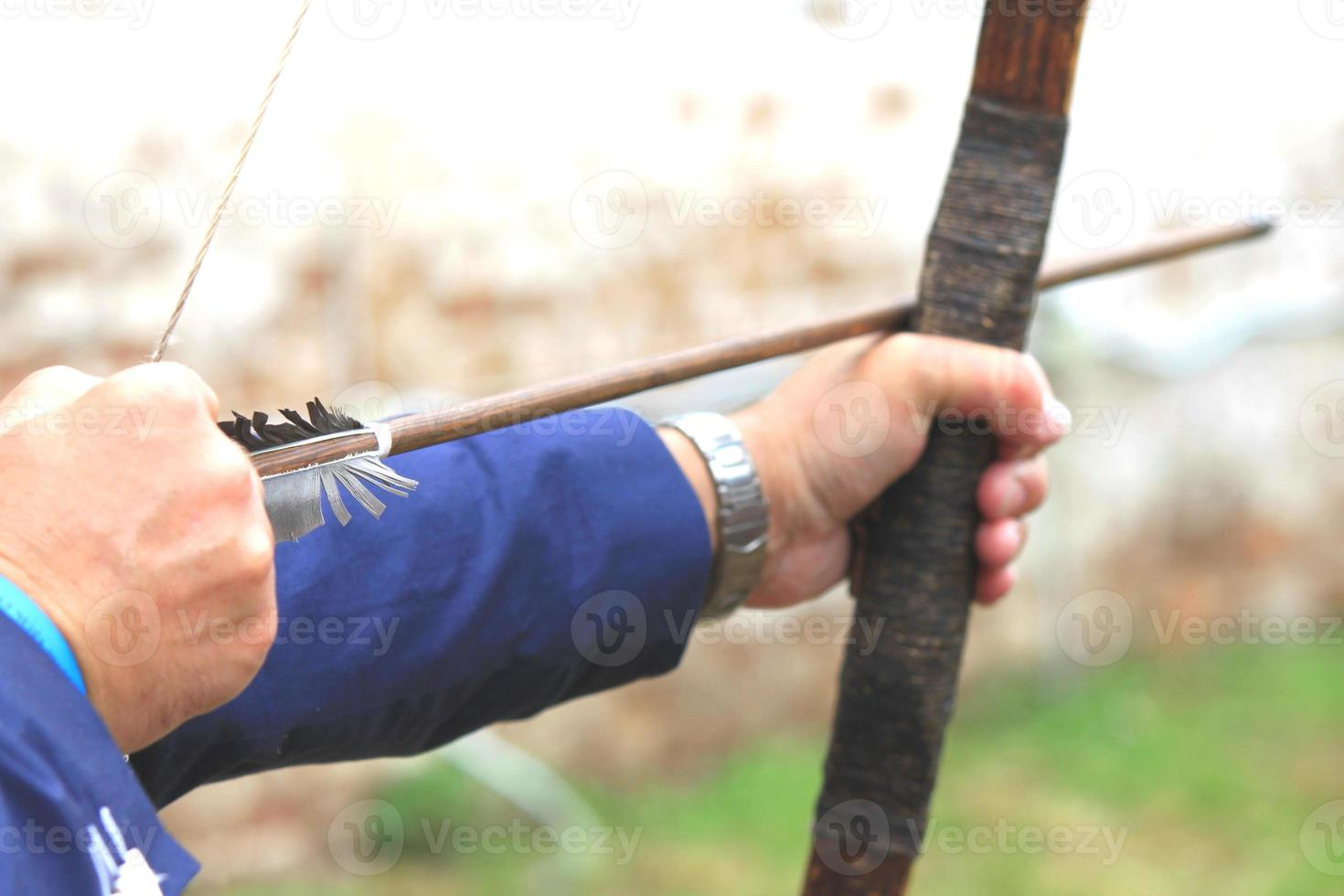Geschäftsmann, der Bogen hält und zum Bogenschießenziel schießt foto