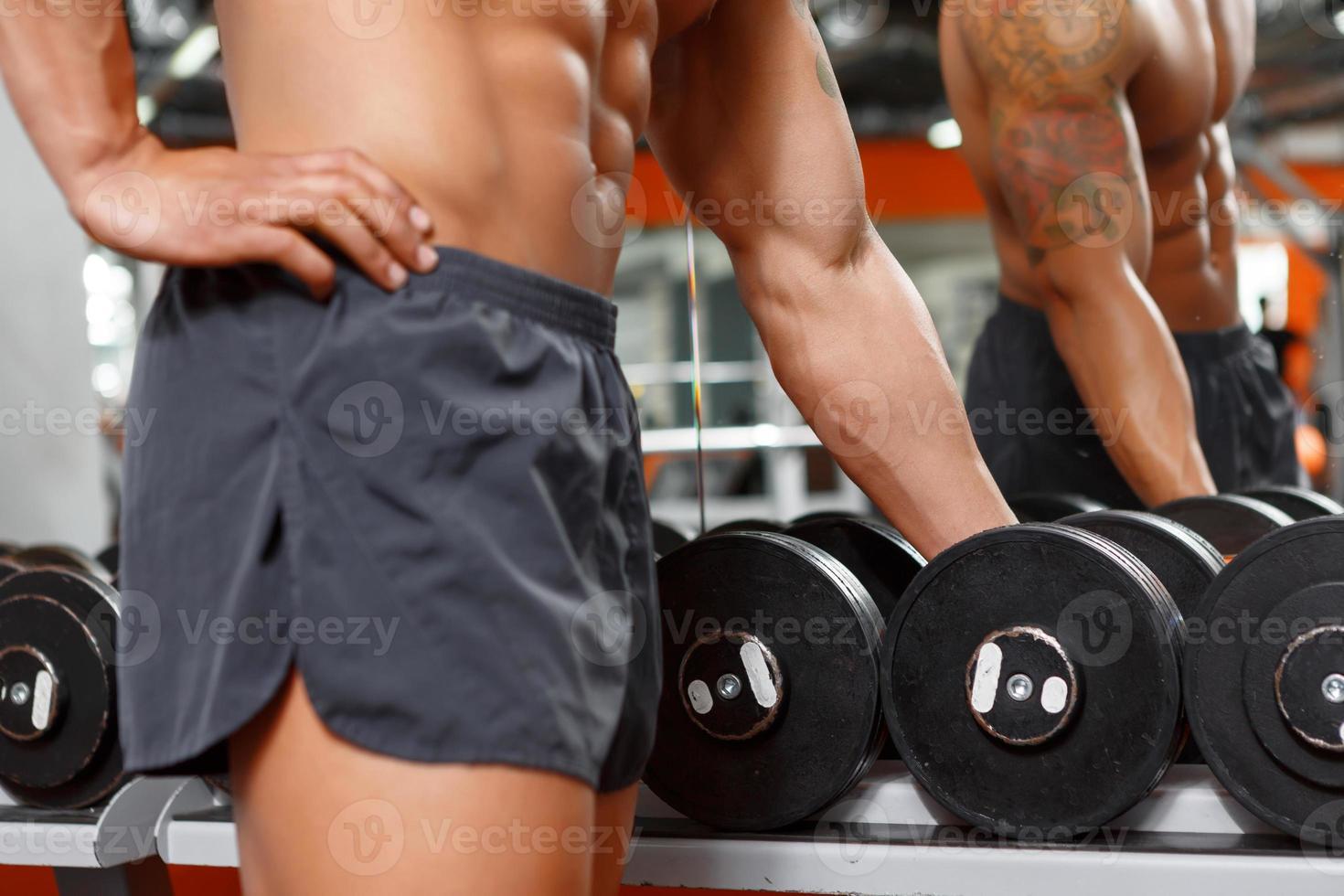muskulöser Mann, der Langhantel im Fitnessstudio wählt foto