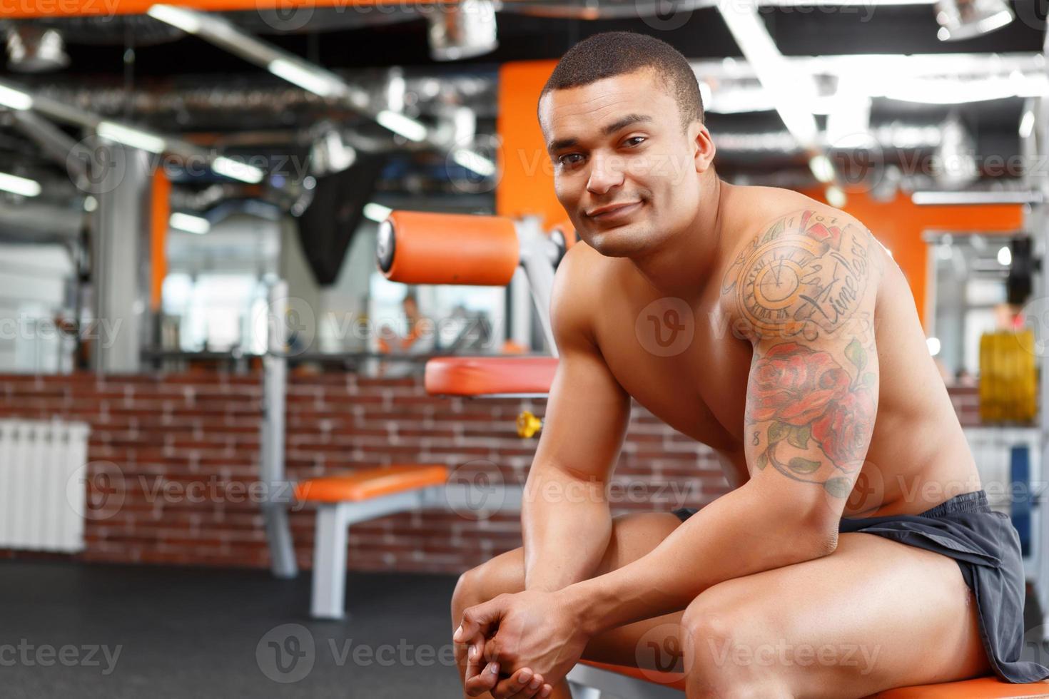 muskulöser Mann sitzt und hält in der Hand foto