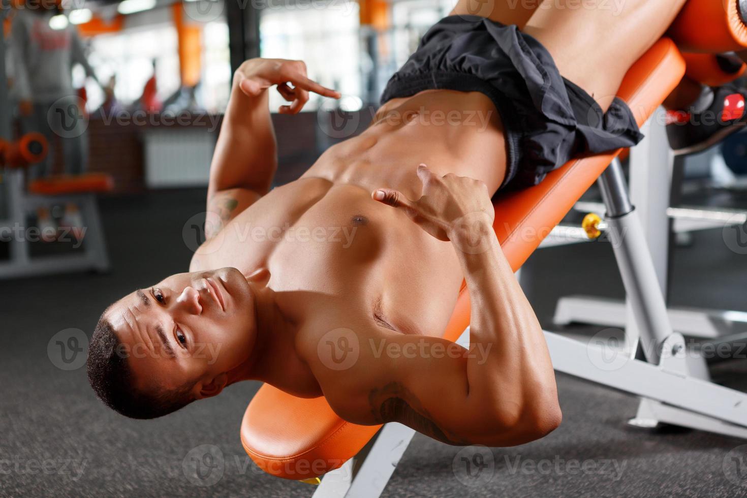 muskulöser Mann, der auf seine Presse zeigt foto
