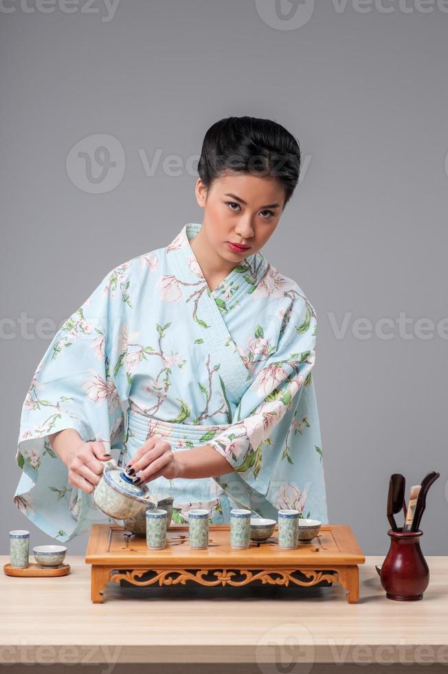 asiatische Schönheit, die sich für die Teezeremonie fertig macht foto