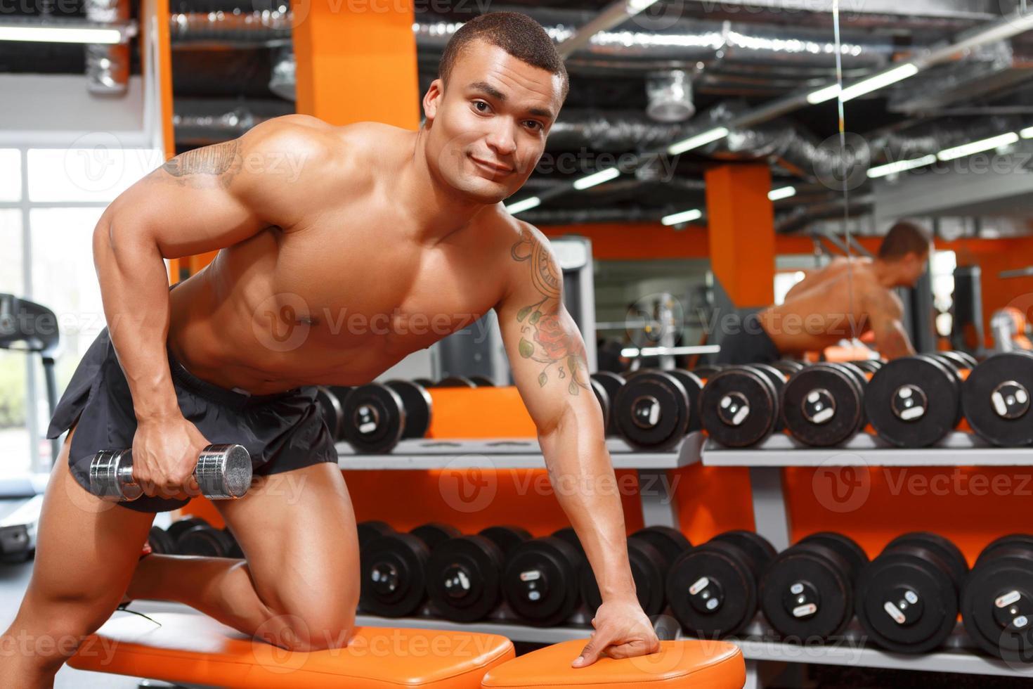 muskulöser Mann, der Übungen mit Hanteln im Fitnessstudio macht foto
