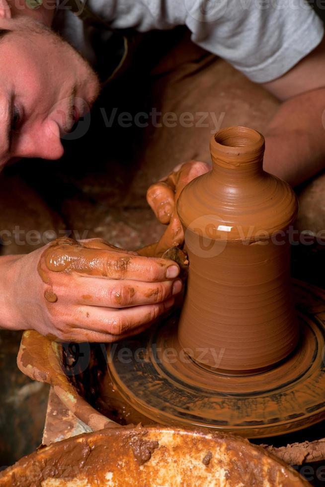 Hände eines Töpfers, die ein irdenes Glas erschaffen foto