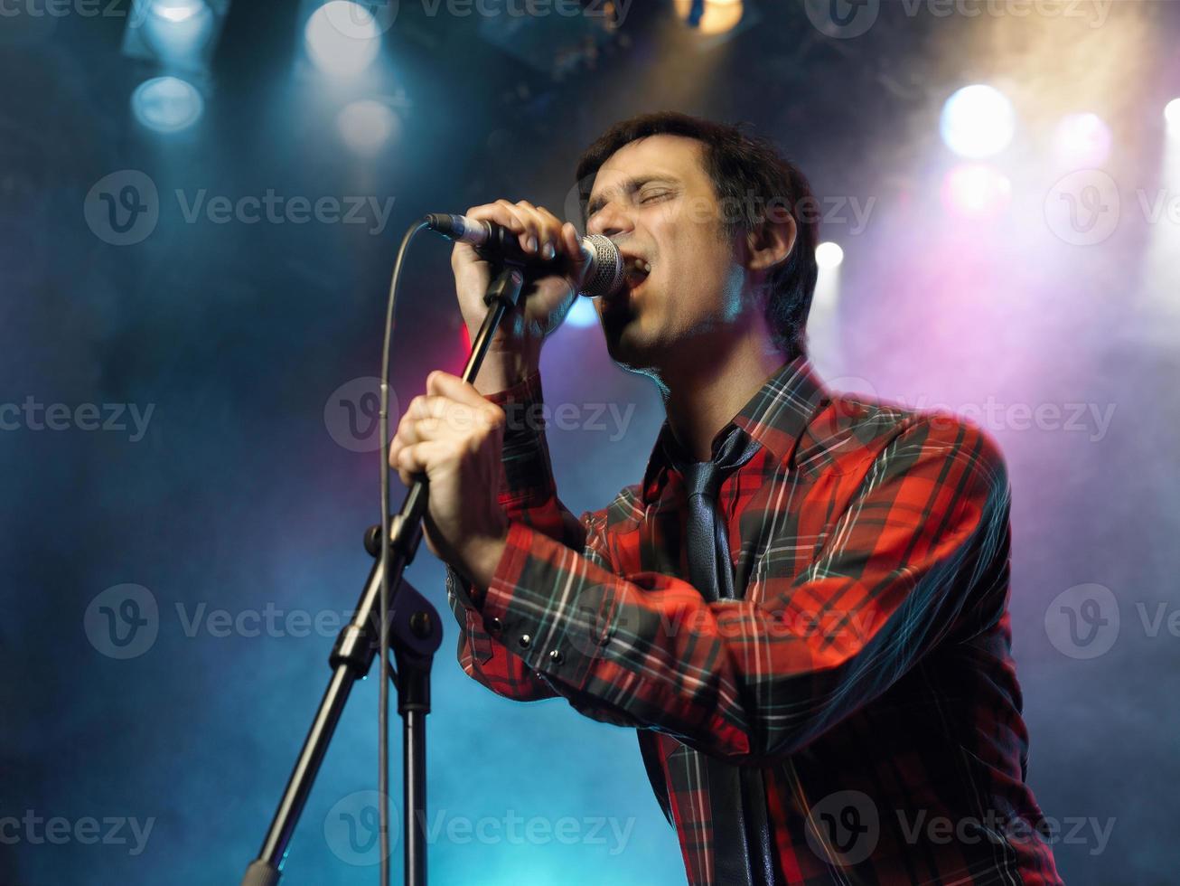 junger Mann singt ins Mikrofon foto
