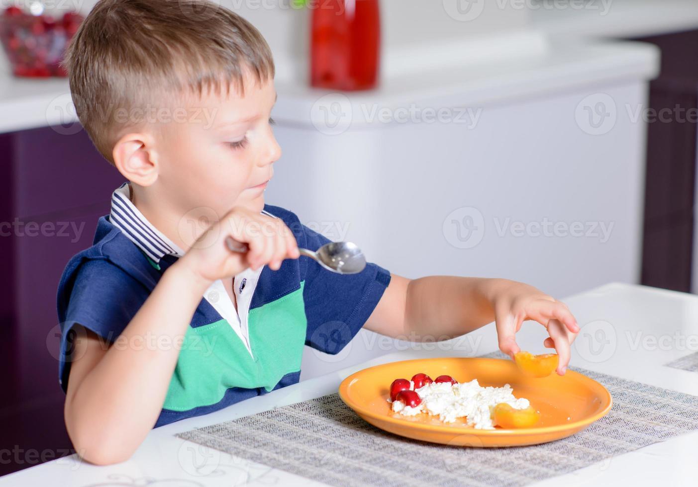 Junge, der Teller mit Käse und Obst isst foto