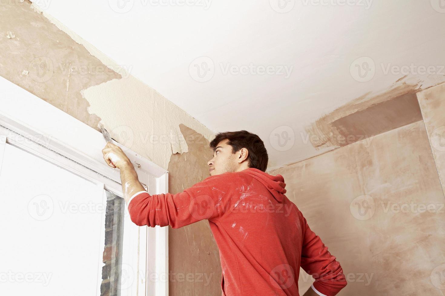 Mann kratzt Farbe von der Wand in unrenoviertem Raum foto