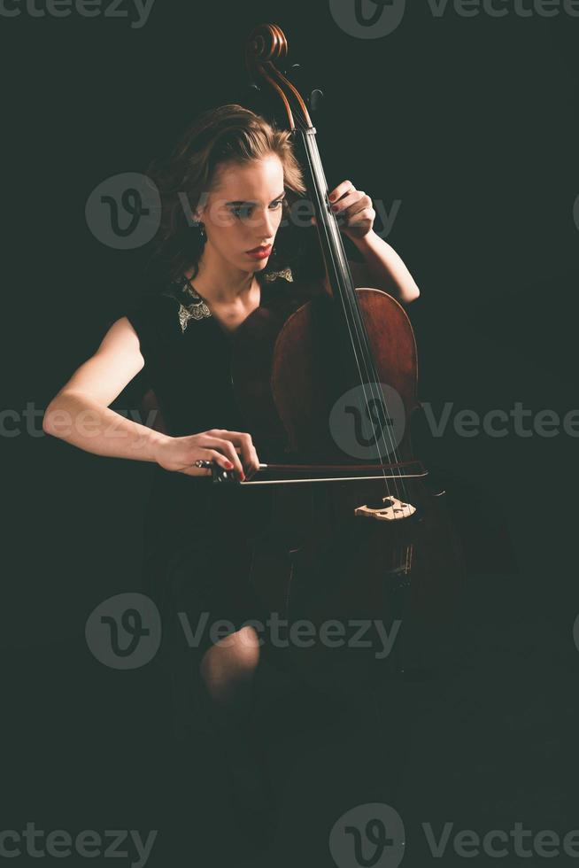 hübsche junge Frau, die nachts Cello spielt foto