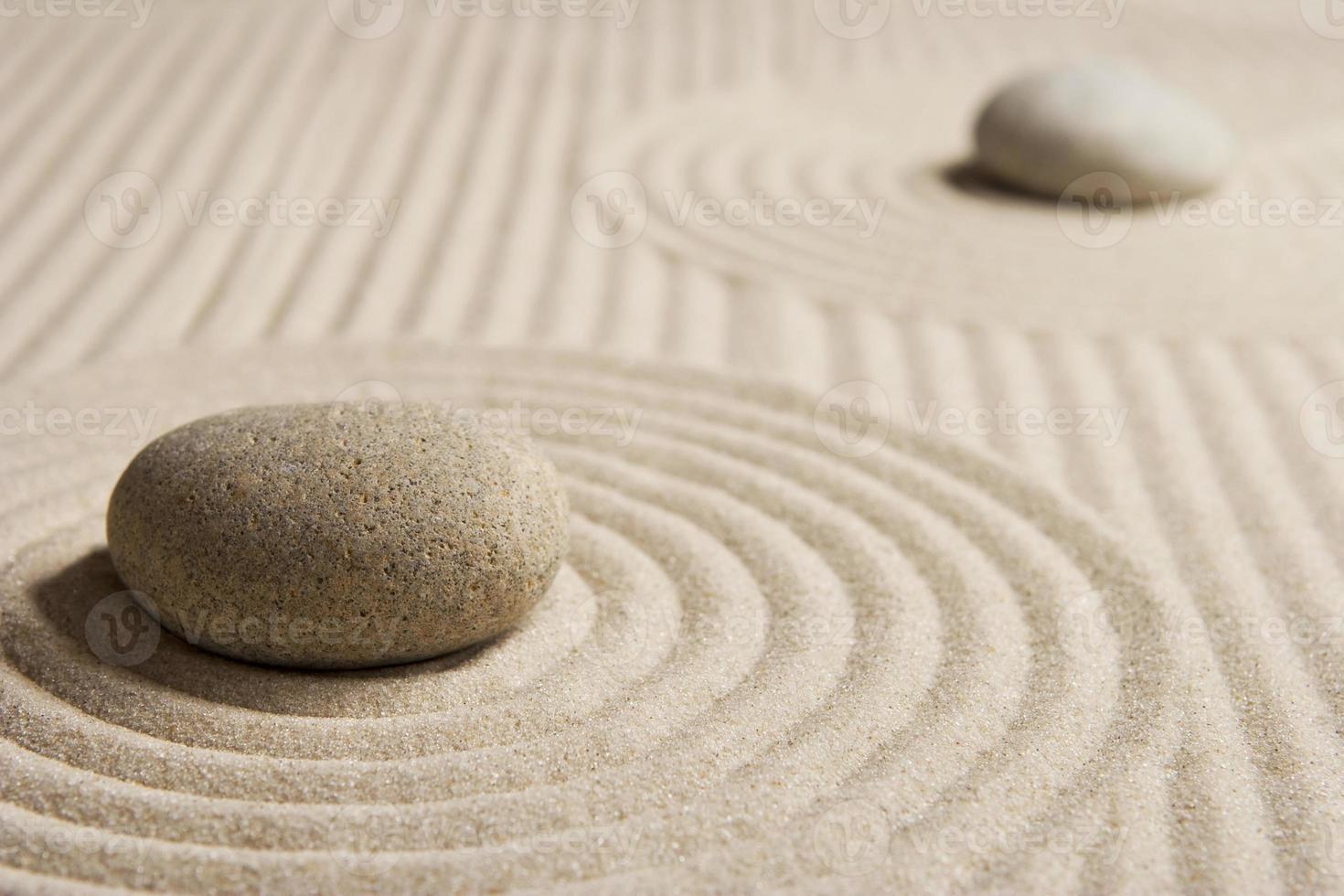 Kieselsteine sitzen in einem geharkten Zen-Garten foto