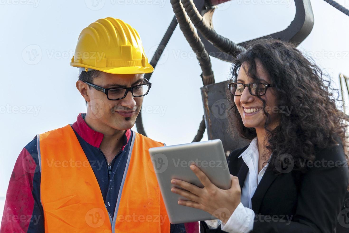 junge Ingenieurin spricht über die Arbeit mit einem Arbeiter foto
