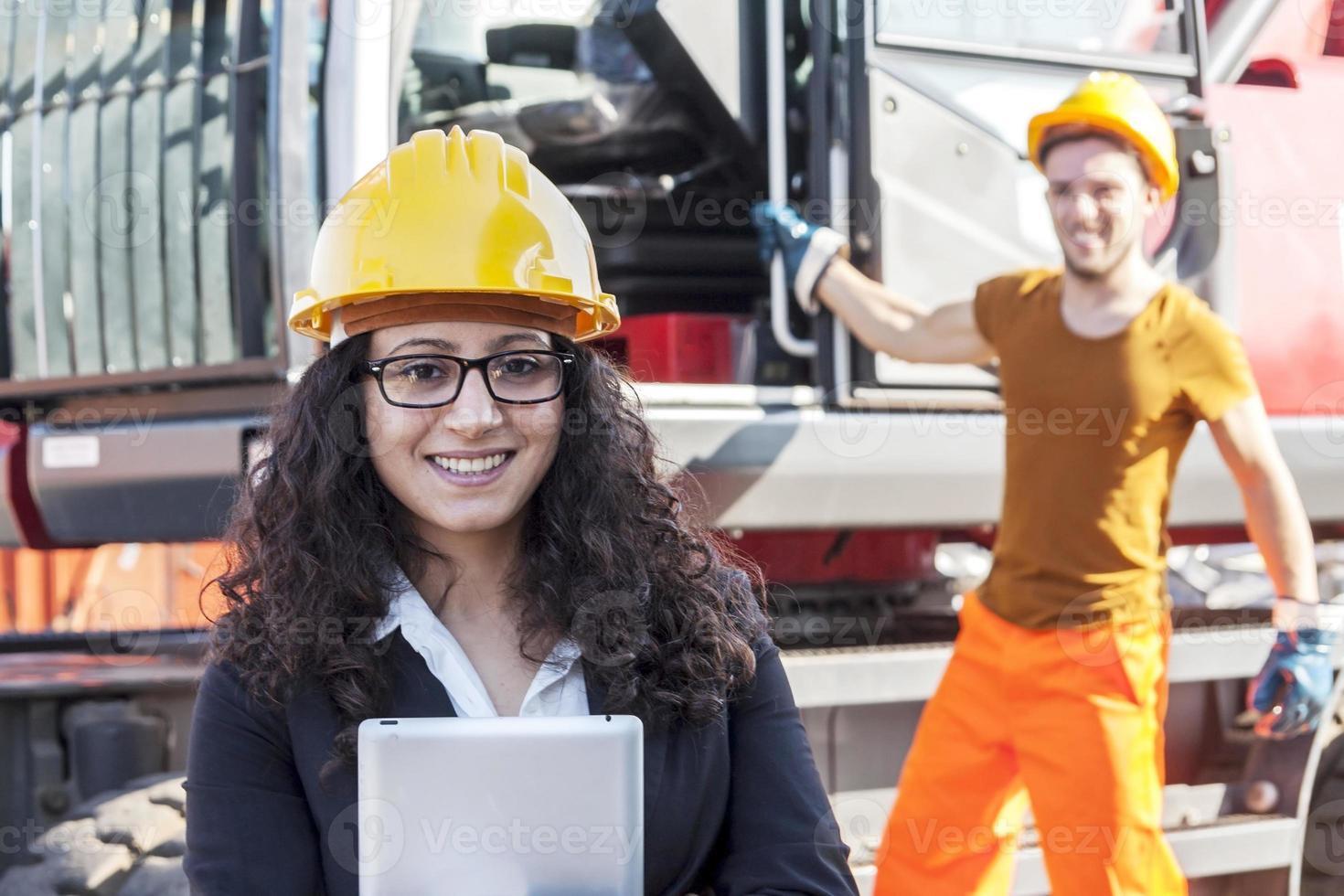 junge Ingenieurin, die im Schrottplatz mit einem Arbeiter aufwirft foto