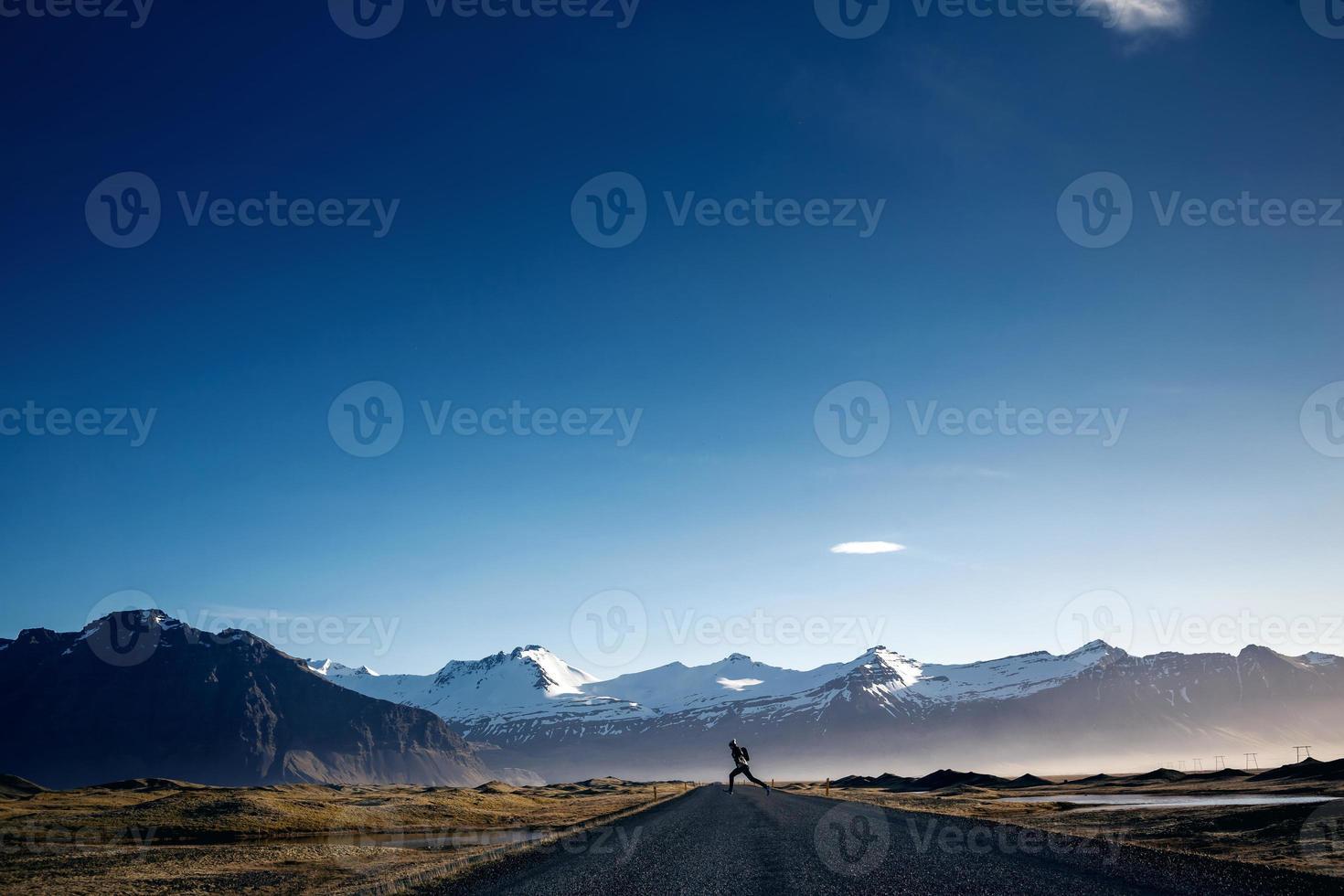 Mann springt auf kurvenreicher Bergstraße foto