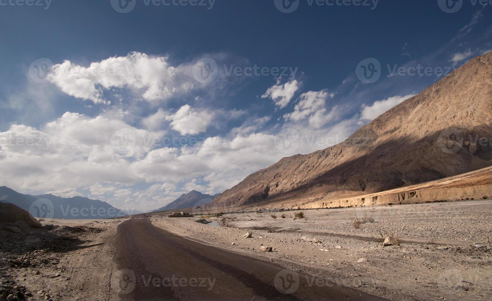 Wüstenstraße mit horizontalem Himmel des Horizonts und weißen Wolken foto