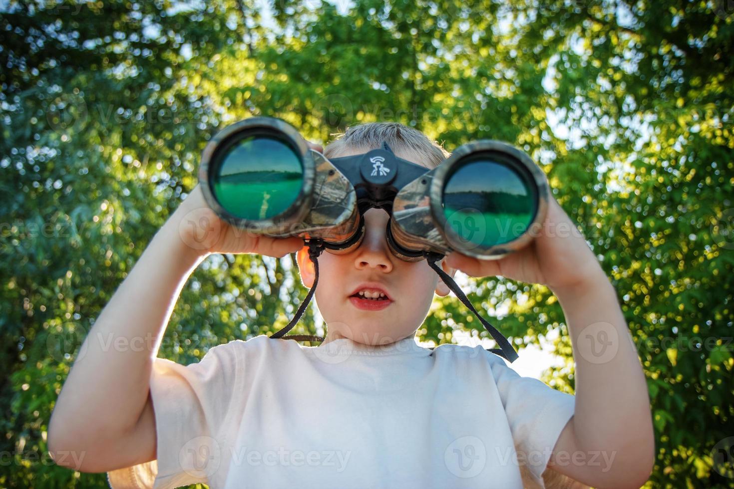 kleiner Junge, der durch ein Fernglas schaut foto