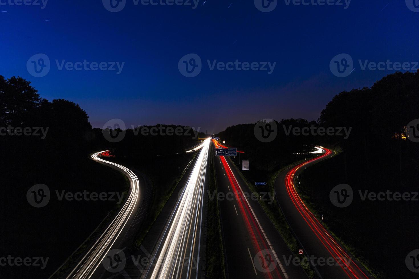 Autolichtspuren an der Autobahnkreuzung bei Nacht foto