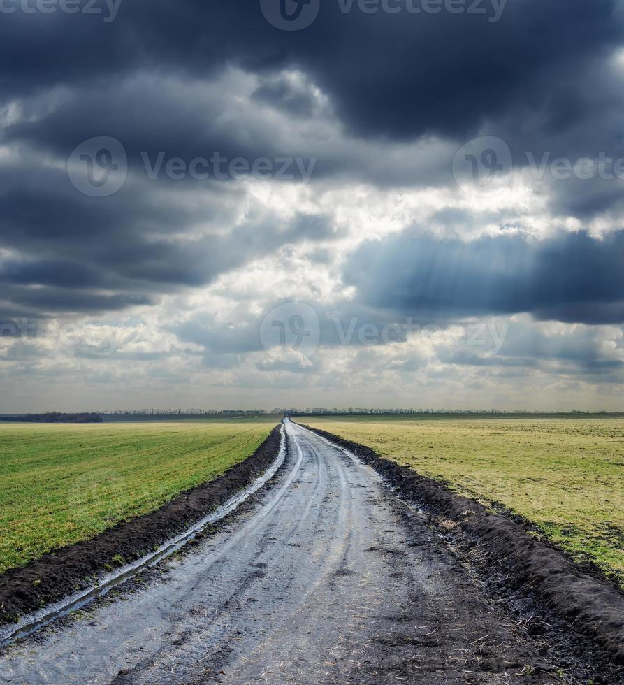 schmutzige Straße zum Horizont und dramatischen Himmel foto