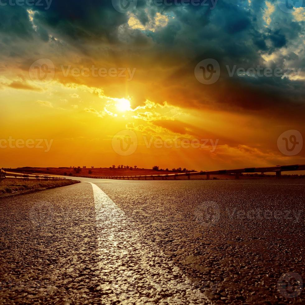 dramatischer Sonnenuntergang und Asphaltstraße zum Horizont foto