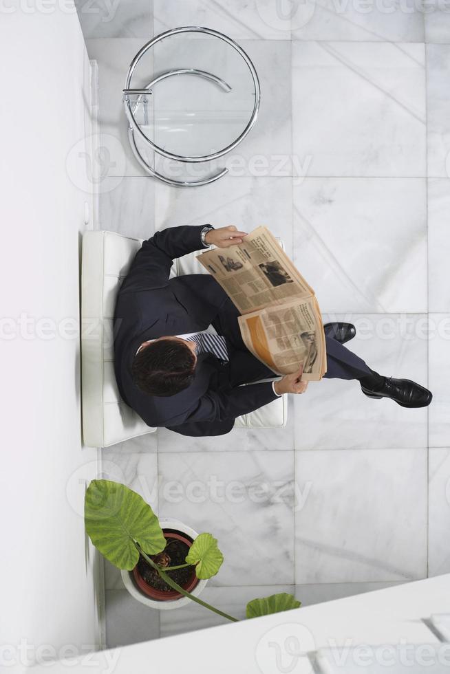 Geschäftsmann, der Zeitung in der Lobby liest foto
